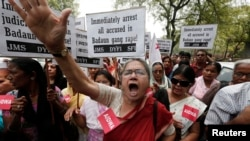 FILE - Demonstrators from All India Democratic Women's Association (AIDWA) hold placards and shout slogans during a protest against the recent killings of two teenage girls, in New Delhi, May 31, 2014.