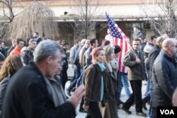"""A man carries an American flag during an anti-government protest in Pristina, Kosovo. Many Kosovars see America as an """"ideal model"""" of democracy, Jan. 9, 2016. (P.W. Wellman/VOA)"""
