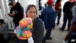 一名妇女手包孩子在等待向美国政府申请政治避难