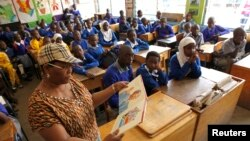FILE - Helen Mashele from South Africa reads the biography of former South African president Nelson Mandela to pupils at Kilimani Primary School in Kenya's capital Nairobi, July 18, 2013.