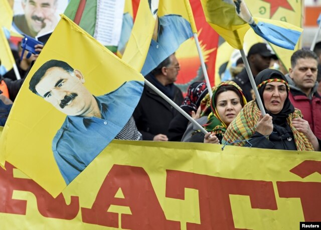 Pro-Kurdish demonstrators carry a flag showing Abdullah Ocalan, the jailed leader of the Kurdistan Workers' Party, as they protest against Turkish authorities during the spring festival of Newroz celebrations in downtown Hanover, Germany, March 19, 2016.