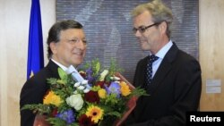 European Commission President Jose Manuel Barroso (L) receives flowers from Atle Leikvoll, Norway's Ambassador to the European Union, at the EC headquarters in Brussels October 12, 2012.