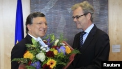 Presiden Komisi Eropa Jose Manuel Barroso (kiri) menerima rangkaian bunga dari Atle Leikvoll, Duta Besar Norwegia untuk Uni Eropa di Brussel (12/10). Uni Eropa memenangkan anugerah Nobel Perdamaian 2012.