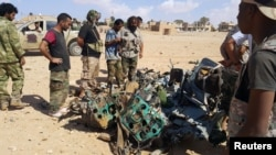 Libyans gather around the remains of a helicopter that crashed near Benghazi, Libya, July 20, 2016.