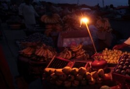 A gas-lamp is seen at a fruit stall during a power outage in Rawalpindi, June 3, 2013.