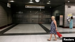 A commuter walks by a closed train station in a northern Athens suburb July 16, 2013. Some central Metro stations remained closed after a police order for safety reasons during a general 24-hour strike in Greece.