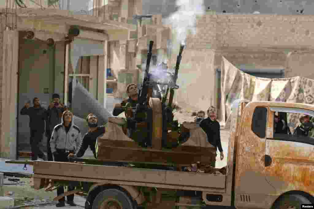 Free Syrian Army fighters fire an anti-aircraft weapon towards forces loyal to Syria's President Bashar al-Assad in the Handarat area, north of Aleppo.