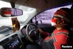 Agus Widanarko, 40, mengenakan kostum Spiderman saat mengemudi saat bersiap menghibur anak-anak yang terkurung di rumah akibat pembatasan COVID-19, di Sukoharjo, Jawa Tengah, 10 September 2021. (Foto: Reuters)