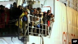 Rescued migrants wait to disembark from an Italian Coast Guard ship in the harbor of Palermo, Sicily, southern Italy, April 14, 2015.