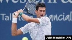 Novak Đoković u duelu sa Francuzom Adrijanom Manarinom u drugom kolu turnira u Sinsinatiju (Foto: AP/John Minchillo)