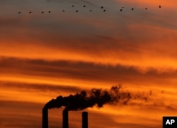 FILE - A flock of Geese fly past the smokestacks at the Jeffrey Energy Center coal power plant as the suns sets near Emmett, Kansas.