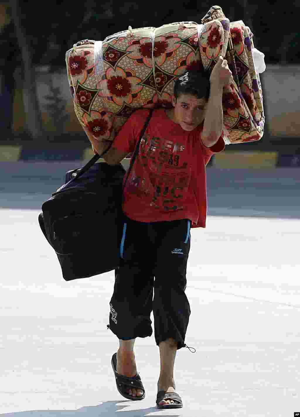지난달 30일 시리아 난민 소년이 짐보따리를 이고 터키 국경 검문소를 지나고 있다.