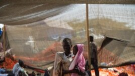 A woman stands with her daughter in the Médecins Sans Frontières (MSF) clinic set up at the camp for displaced people in the grounds of the United Nations Mission to South Sudan (UNMISS) base in Juba, South Sudan, on January 12, 2014.