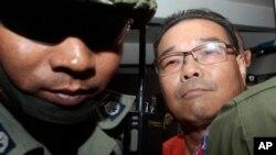 Hong Sok Hour (kanan), senator oposisi Kamboja, dikawal ketat oleh polisi di Phnom Penh (Foto: dok).