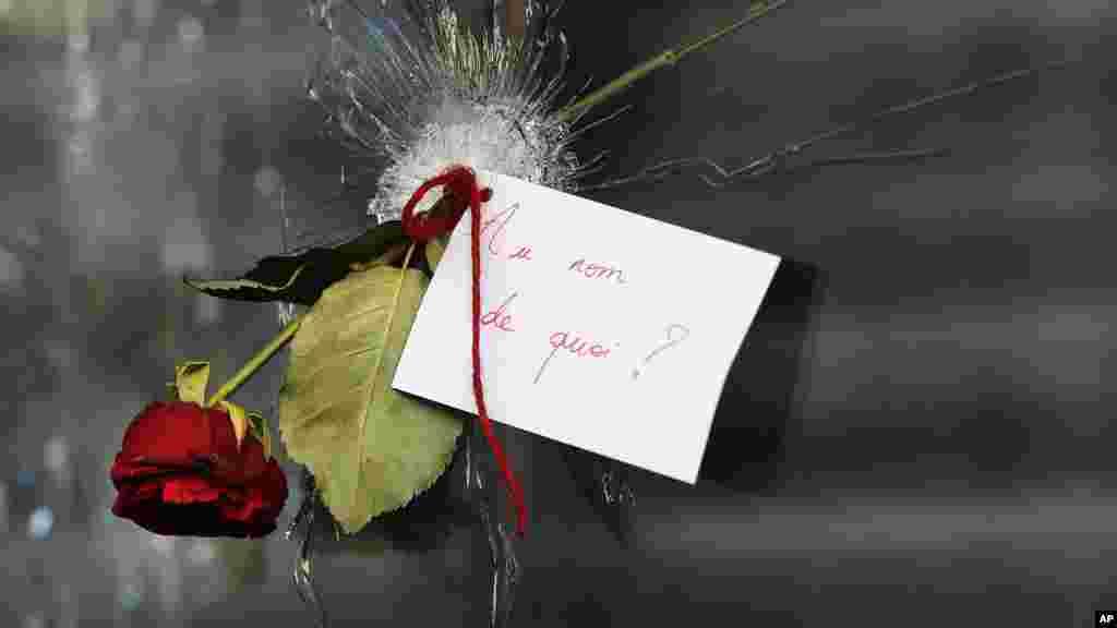 """ጥይት በበሳው መስታወት ሰዎች ሃዘናቸውን ሲገልጹ """"በምን ስም?"""" ወይም በእንግሊዝኛ """"In the name of what?"""" የሚል በፈረንሳይኛ የተፃፈ ጥያቄ አቅርበዋል። ይህ በፓሪስ የሽብር ጥቃት ከደረሰባቸው ቦታዎች አንዱ ሩ ደ ሻሮን (Rue de Charonne) የሚባል ምግብ ቤት ነው። [አሶሽየትድ ፕረስ ፎቶ/AP Photo/ፍራንክ አጎስቲን/Frank Augstein]"""