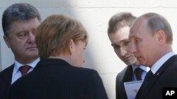 俄罗斯总统普京(右)6月6日在法国诺曼底与乌克兰当选总统波罗申科(左)交谈