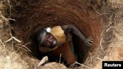 Un 'creuseur' s'introduit dans un trou à la recherche d'or dans le village de Bouafle, près de la frontière entre le Ghana et la Côte d'Ivoire, 18 mars 2014.