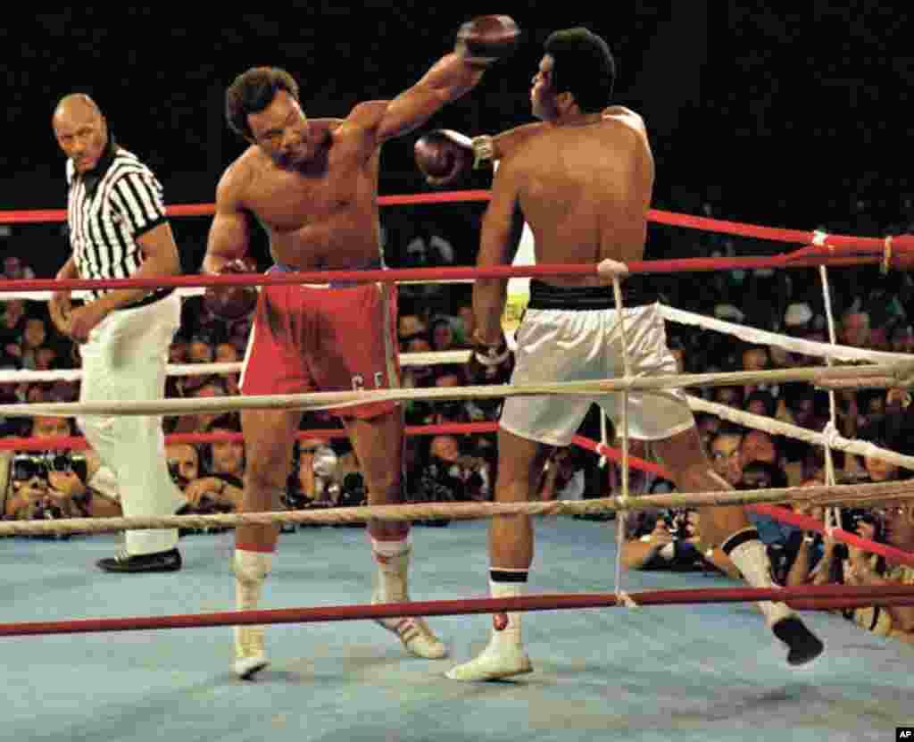Muhammad Ali, kanan, menghindar pukulan George Foreman, mengenakan celana merah, di Kinshasa, Zaire, 30 Oktober 1974. Ali menang KO pada ronde kedelapan pada pertandingan di Afrika tersebut dengan wasit Zack Clayton.
