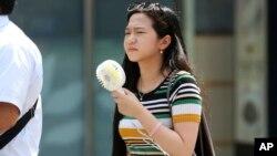 Жінка тримає в руках портативний вентилятор у діловому районі Токіо, 23 липня 2018 року.