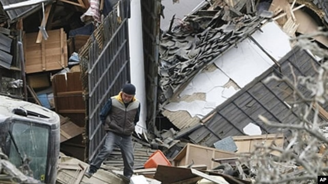A man walks on the debris in Ishinomaki city, Miyagi prefecture after a powerful 7.1 aftershock rocked that area of Japan, April 8, 2011