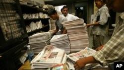 Seorang pekerja di sebuah kantor distribusi koran dan majalah di New Delhi, India (tengah belakang) tengah melayani seorang pelanggan (Foto: dok).