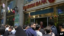 Iranians stand in front of a bank, hoping to buy U.S. dollars at the new official exchange rate announced by the government, in downtown Tehran, April 10, 2018. Iran moved this week to enforce a single exchange rate to the dollar, banning all unregulated trading.