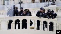 پلیس کنگره تظاهرکنندگان را که تلاش می کردند موانع پلیس را پشت سر بگذراند زیر نظر دارند. واشنگتن، ۶ ژانویه ۲۰۲۱
