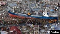 Warga setempat mengamati kapal yang terhempas topan Haiyan di tengah kota Tacloban Filipina tengah (21/11).