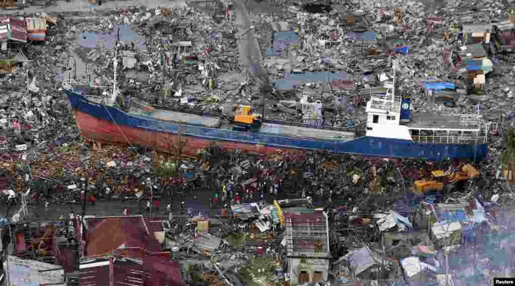 Residents look at a ship that was swept by Typhoon Haiyan nearly two weeks ago, in downtown Tacloban city in central Philippines, Nov. 21, 2013.