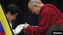 The Dalai Lama gives a Tibetan shawl to Japan's main opposition Liberal Democratic Party president Shinzo Abe, at the upper house members' office building in Tokyo, November 13, 2012.