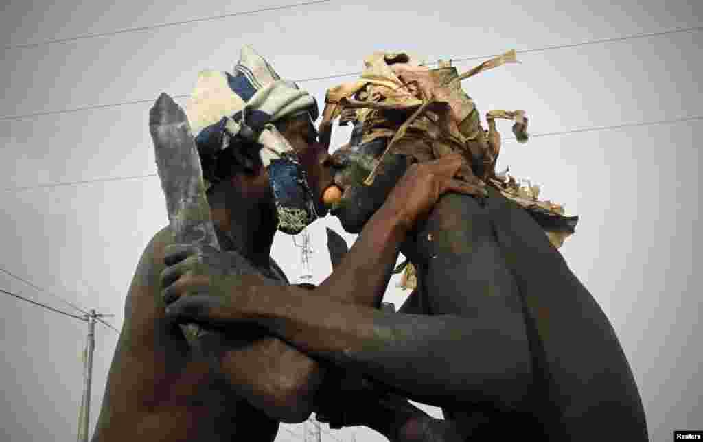 شرکت کنندگان در مراسم مذهبی کارناوال پوپو (ماسک) در بونوئيا (در شرق ابيجان در ساحل عاج) تخم مرغی را دهان بهدهان میکنند.