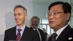 ທ່ານ Tom Curley ປະທານອົງການຂ່າວ AP (ຊ້າຍ) ແລະທ່ານ Kim Pyong Ho ປະທານ ສໍານັກງານສູນກາງຂ່າວເກົາຫລີເໜືອ ຖືປ້າຍອົງການຂ່າວ Associated Press ທີ່ກຸງພຽງຢ້າງ. ວັນທີ 16 ມັງກອນ 2012.