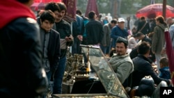自从发生天安门汽车袭击案后,北京一处露天文物市场的维吾尔玉器商贩每天都被警察检查身份证。(资料照)