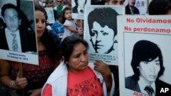 La gente lleva fotos de las víctimas de la dictadura de 1976-83, durante una marcha que conmemora el 41 aniversario del golpe militar en Buenos Aires, Argentina, el viernes 24 de marzo de 2017.