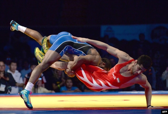ordan Burroughs of the United States takes down Ezzatollah Akbari Zarinkolaei of Iran during the 2014 FILA Freestyle Wrestling World Cup on March 15, 2014 in Inglewood, California.