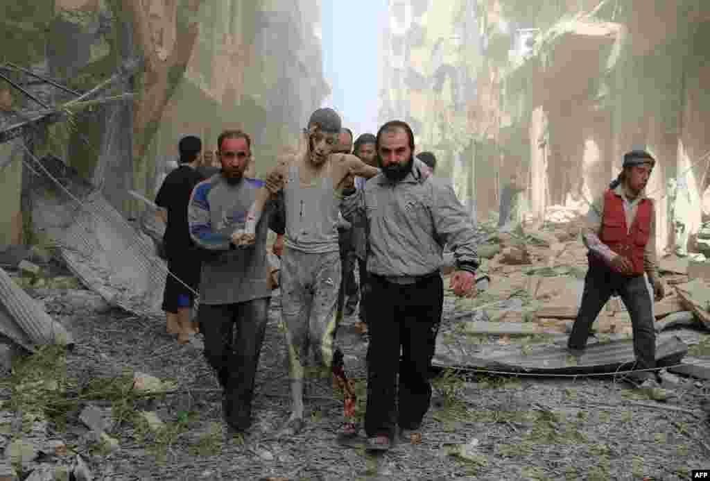 ពលរដ្ឋស៊ីរីជួយយុវជនរងរបួសមួយ នៅក្រោយការវាយប្រហារតាមអាកាសនៅលើក្រុមឧទ្ទាម Fardous ដែលត្រូវបានធ្វើឡើងនៅសង្កាត់មួយក្នុងក្រុង Aleppo។
