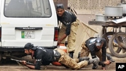 Pakistani police commandos take position outside one of the two stormed mosques by gunmen in Lahore, 28 May 2010