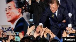 문재인 한국 대통령 당선인이 9일 서울 광화문 광장에 모인 지지자들의 손을 잡아주고 있다.