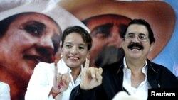 El expresidente de Honduras Manuel Zelaya y su esposa Xiomara, candidata a la presidencia, muestran sus dedos entintados luego de las primarias hondureñas.