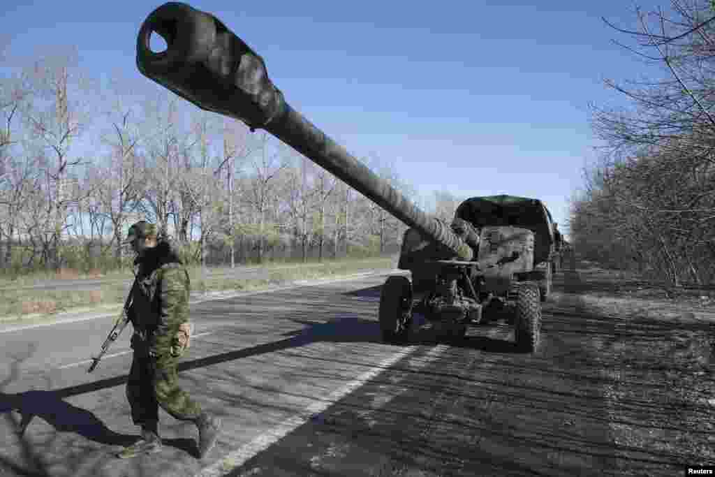 An armed man stands near a truck towing a mobile artillery cannon as rebels with the separatist self-proclaimed Donetsk people's republic army pull back from Donetsk, Feb. 24, 2015.