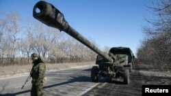 An armed man stands near a truck towing an artillery piece as rebels with the separatist self-proclaimed Donetsk People's Republic Army pull back from Donetsk, Ukraine, Feb. 24, 2015.