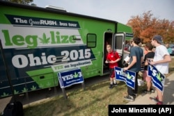 This October 23, 2015 file photo shows college students collecting lawn signs and shirts at a promotional tour bus from ResponsibleOhio, a pro-marijuana legalization group, at Miami University, in Oxford, Ohio.