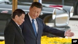 FILE - Chinese President Xi Jinping, right, shows the way to Philippine President Rodrigo Duterte during a welcome ceremony outside the Great Hall of the People in Beijing, China, Thursday, Oct. 20, 2016. (AP Photo/Ng Han Guan)