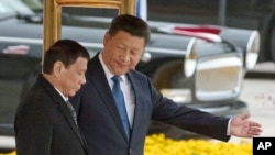 Chinese President Xi Jinping, right, and Philippine President Rodrigo Duterte are seen during a welcome ceremony outside the Great Hall of the People in Beijing, China, Oct. 20, 2016.