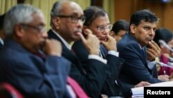 FILE - The Reserve Bank of India (RBI) Governor Raghuram Rajan and other officials listen to a question during a news conference after the bi-monthly monetary policy review in Mumbai, Dec. 2, 2014.