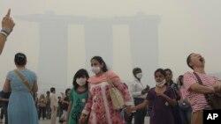 Turis di Singapura memakai masker karena asap yang memenuhi udara, saat krisis polusi memuncak Juni 2013.