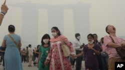 Tourists visit a sightseeing spot as the Marina Bay Sands Hotel in the background is shrouded with haze in Singapore, June 22, 2013.