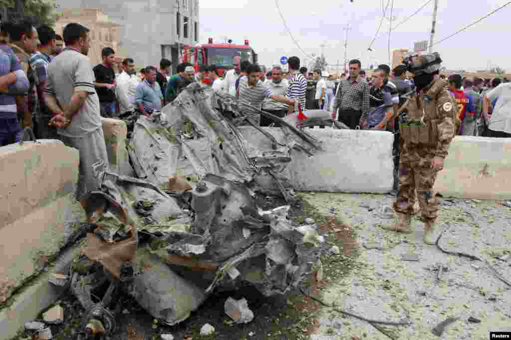 An Iraqi soldier looks at the wreckage of a car after a car bomb attack in Kirkuk, Iraq, May 8, 2013.