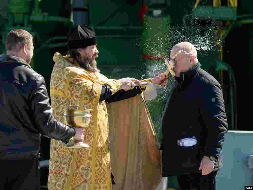 An Orthodox Priest blesses Sergey Semchenko of the Russian Search and Recovery Forces after having blessed the Soyuz rocket at the Baikonur Cosmodrome Launch pad in Kazakhstan.