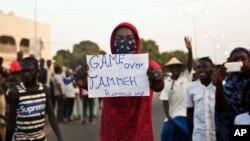 """Manifestante exibe, em Serrekunda, Gâmbia, um cartaz com os dizeres """"Fim da picada, Jammeh"""""""